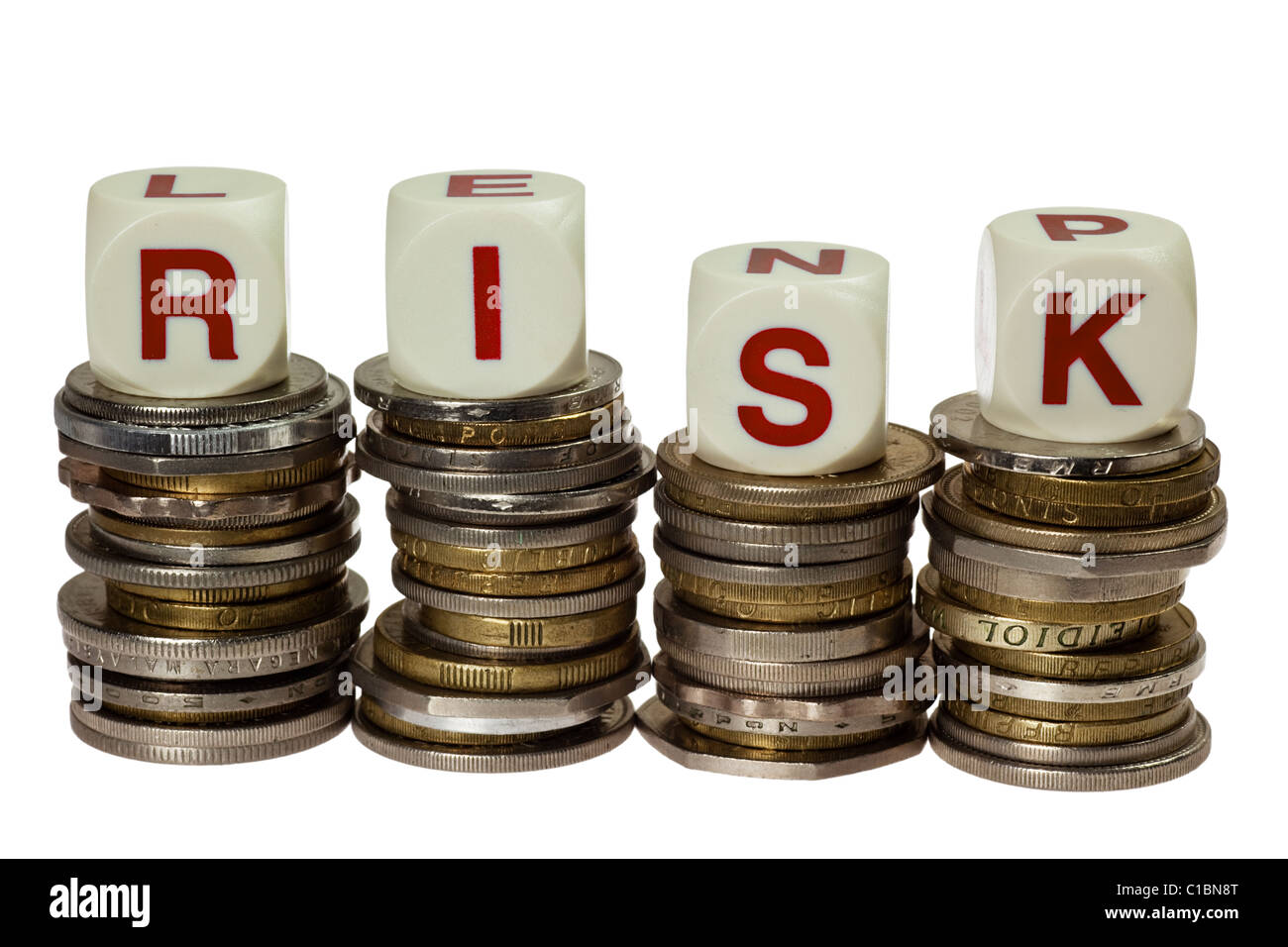 Stacks of coins with the word RISK isolated on white background - Stock Image