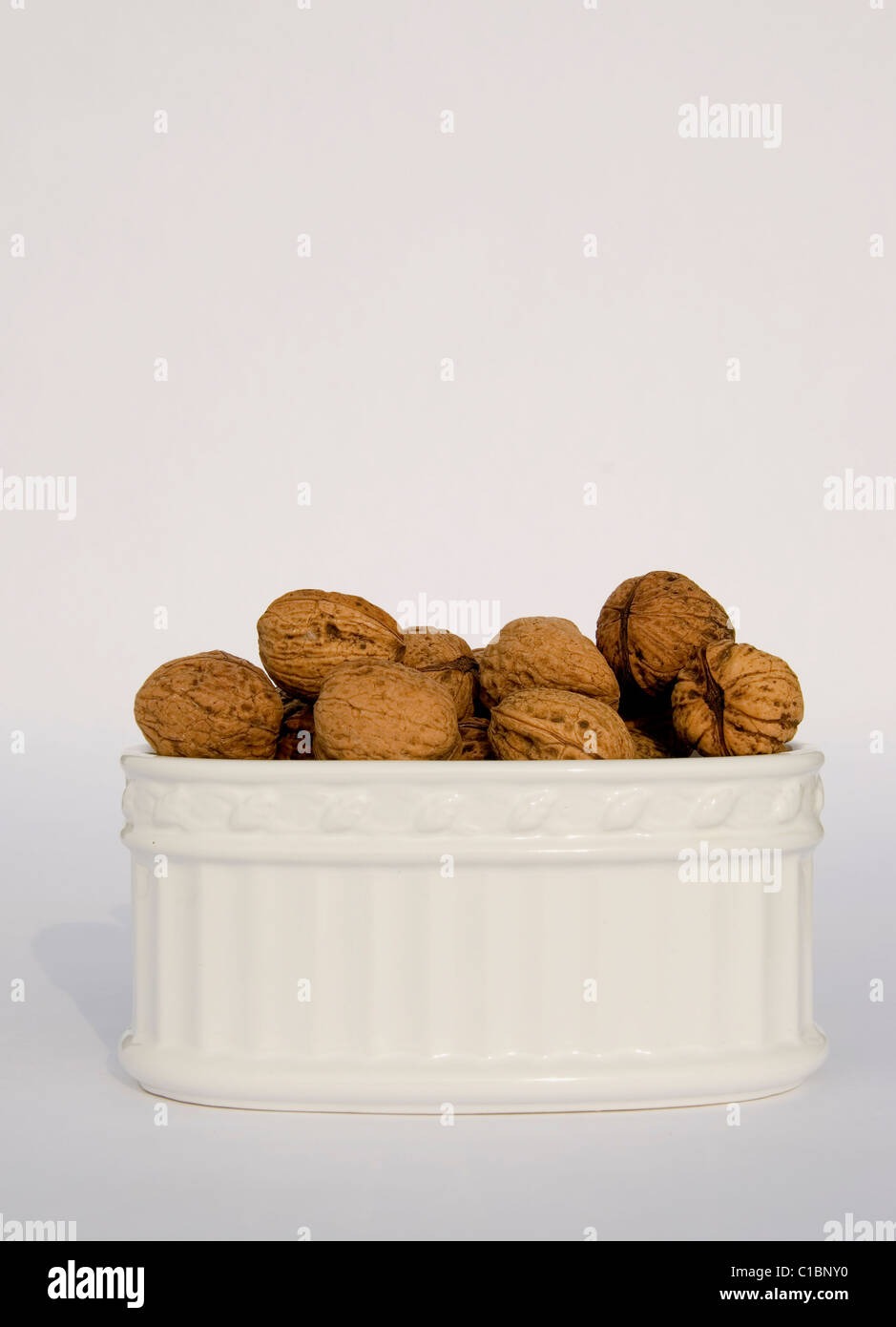 Box of different sizes walnuts isolated on a white background - Stock Image