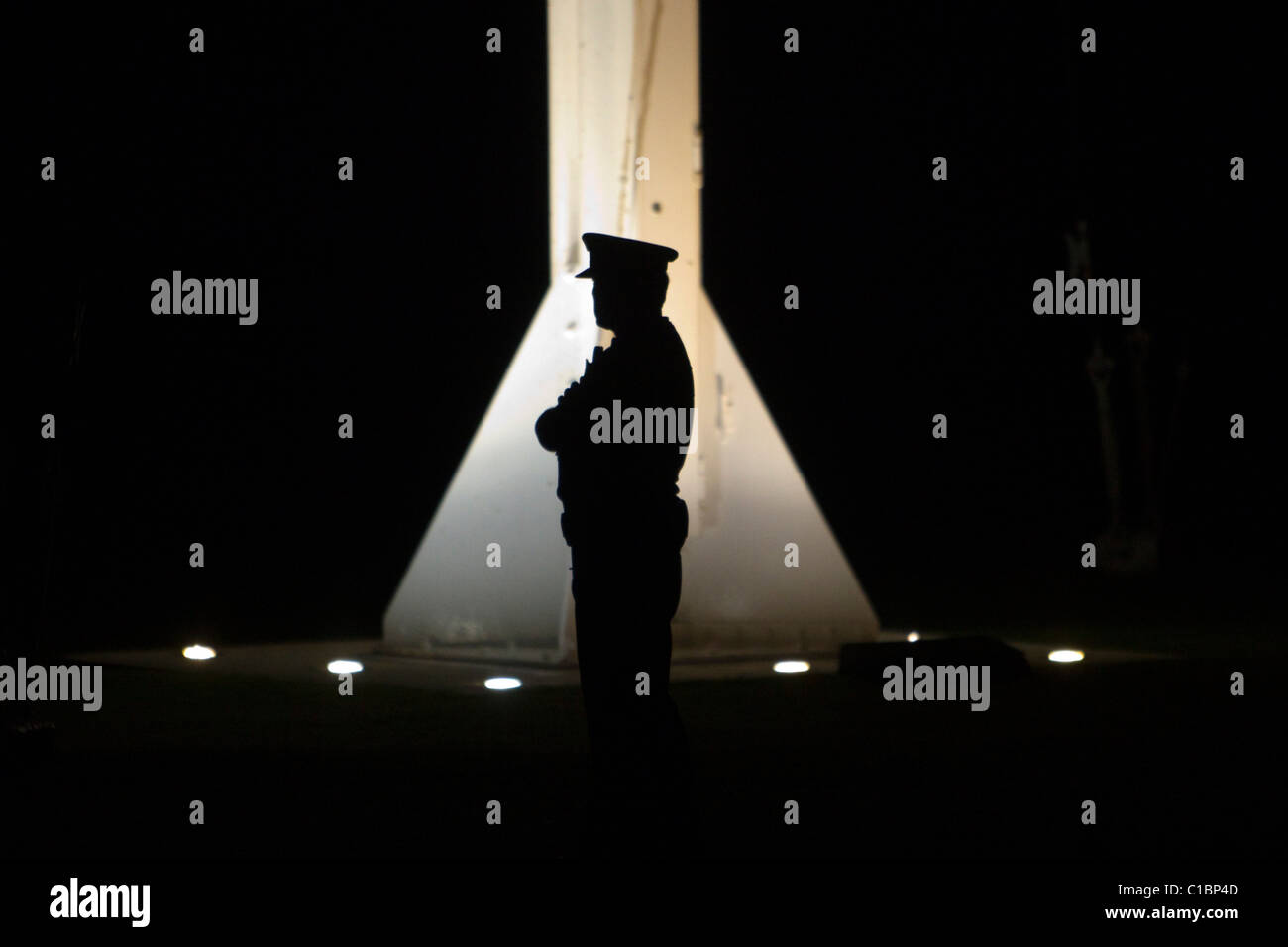 A lone police officer guards the flagpole as the Prime Minister John Key attends the Dawn Service - Stock Image