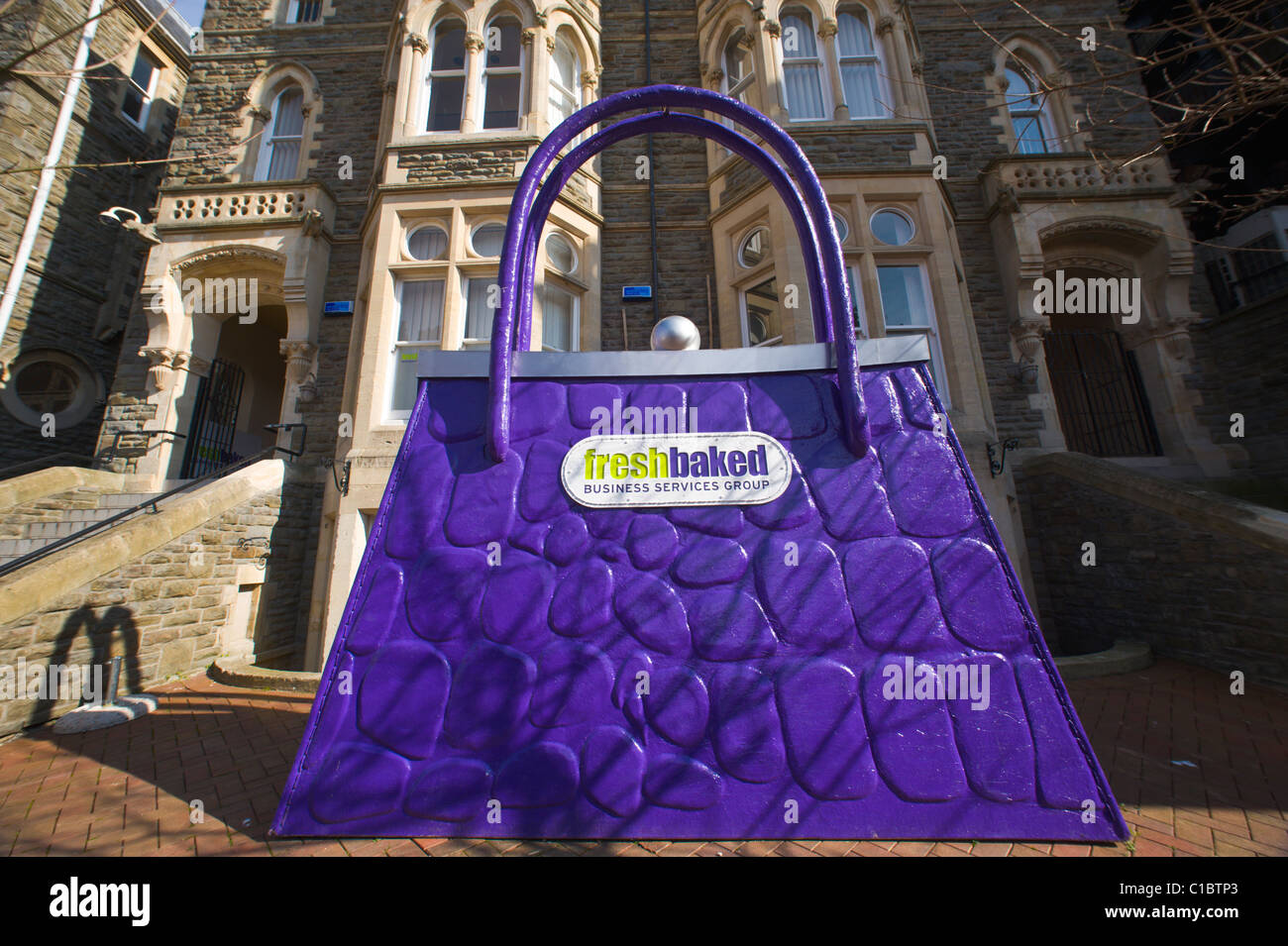 Enormous promotional purple handbag outside offices of a business services group in Cardiff South Wales UK - Stock Image