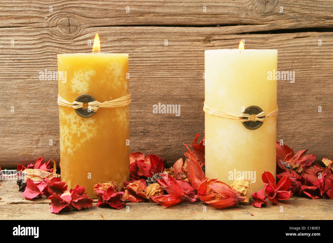 Two burning feng shui candles with dried flowers on a background of old wood - Stock Image