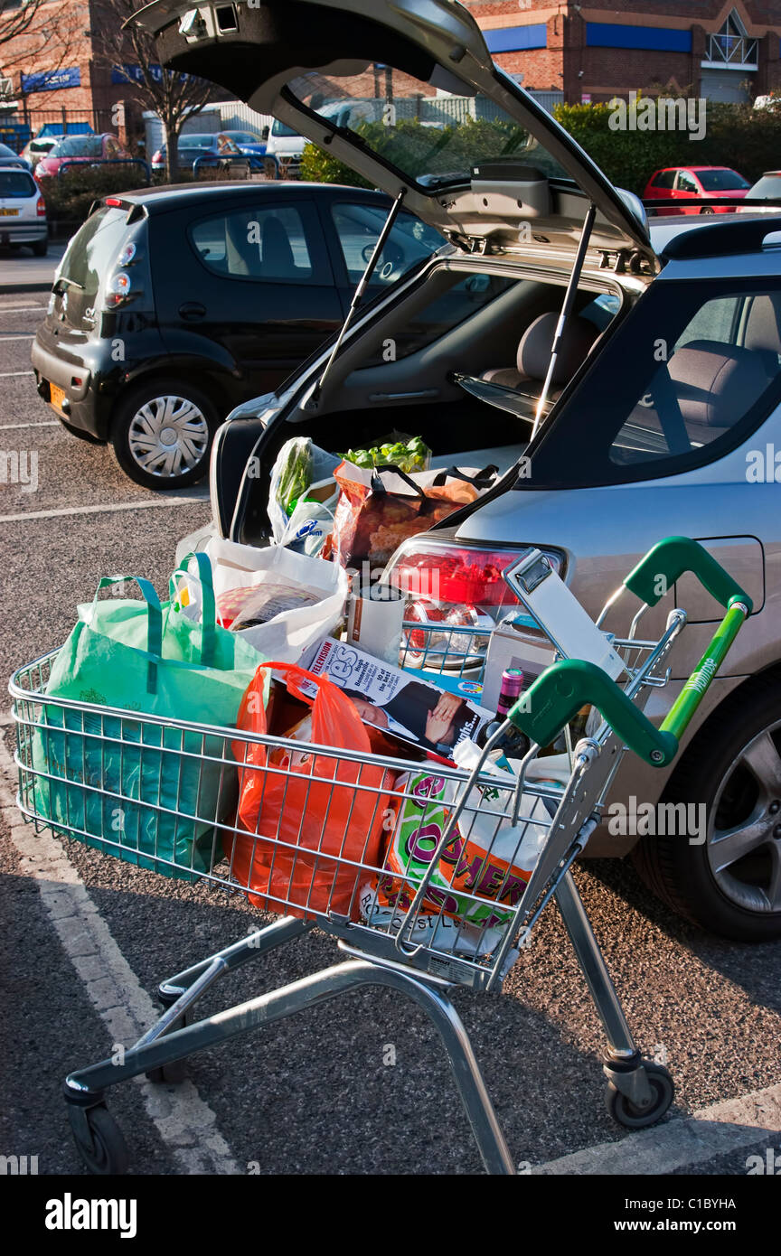 Loading shopping from supermarket trolley into car - Stock Image