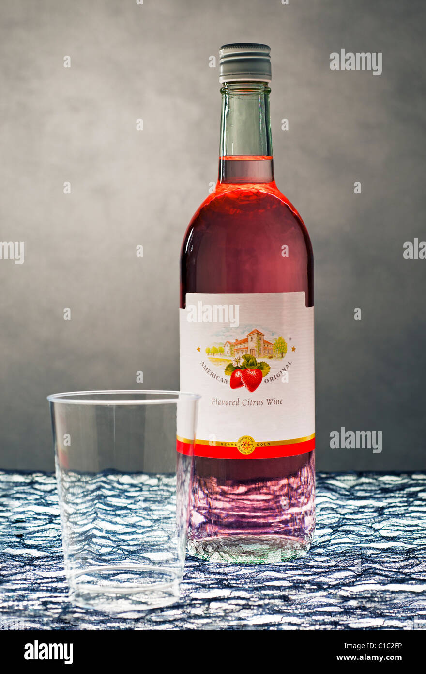 Cheap Strawberry Wine with brand removed from label and a plastic cup. - Stock Image
