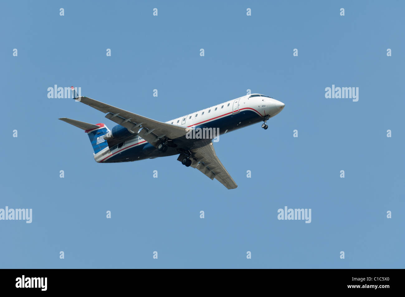 Canadair CL600 regional jet with U.S. Airways livery colours on final approach. - Stock Image