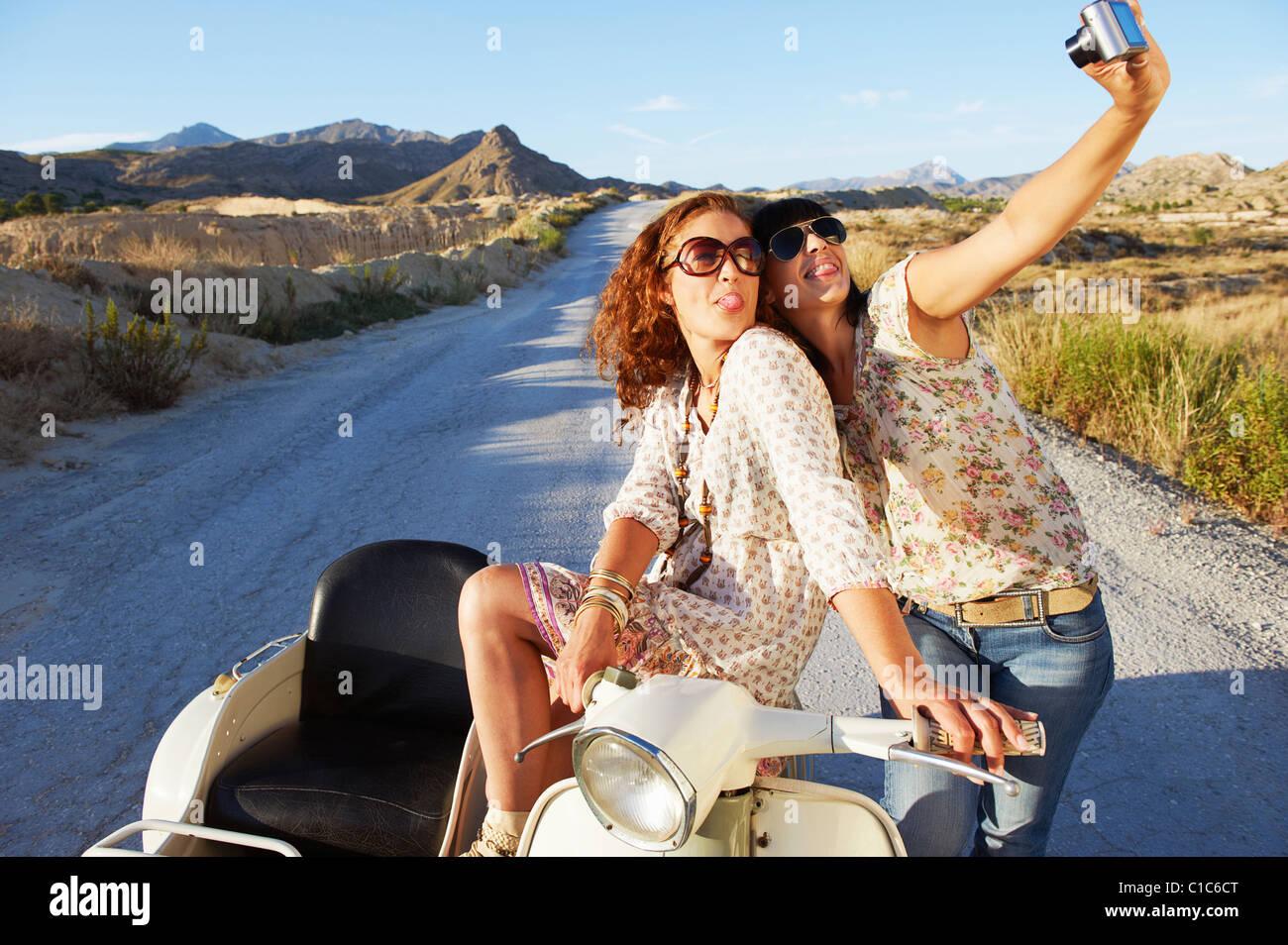 Women on motorbike taking photos - Stock Image