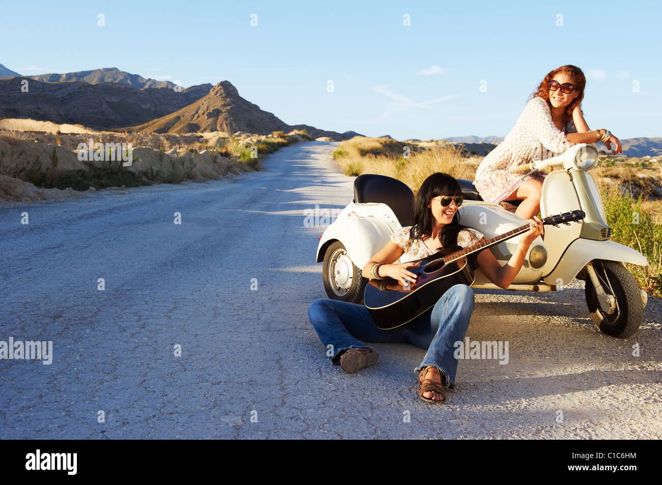 Women resting by road with motorbike - Stock Image