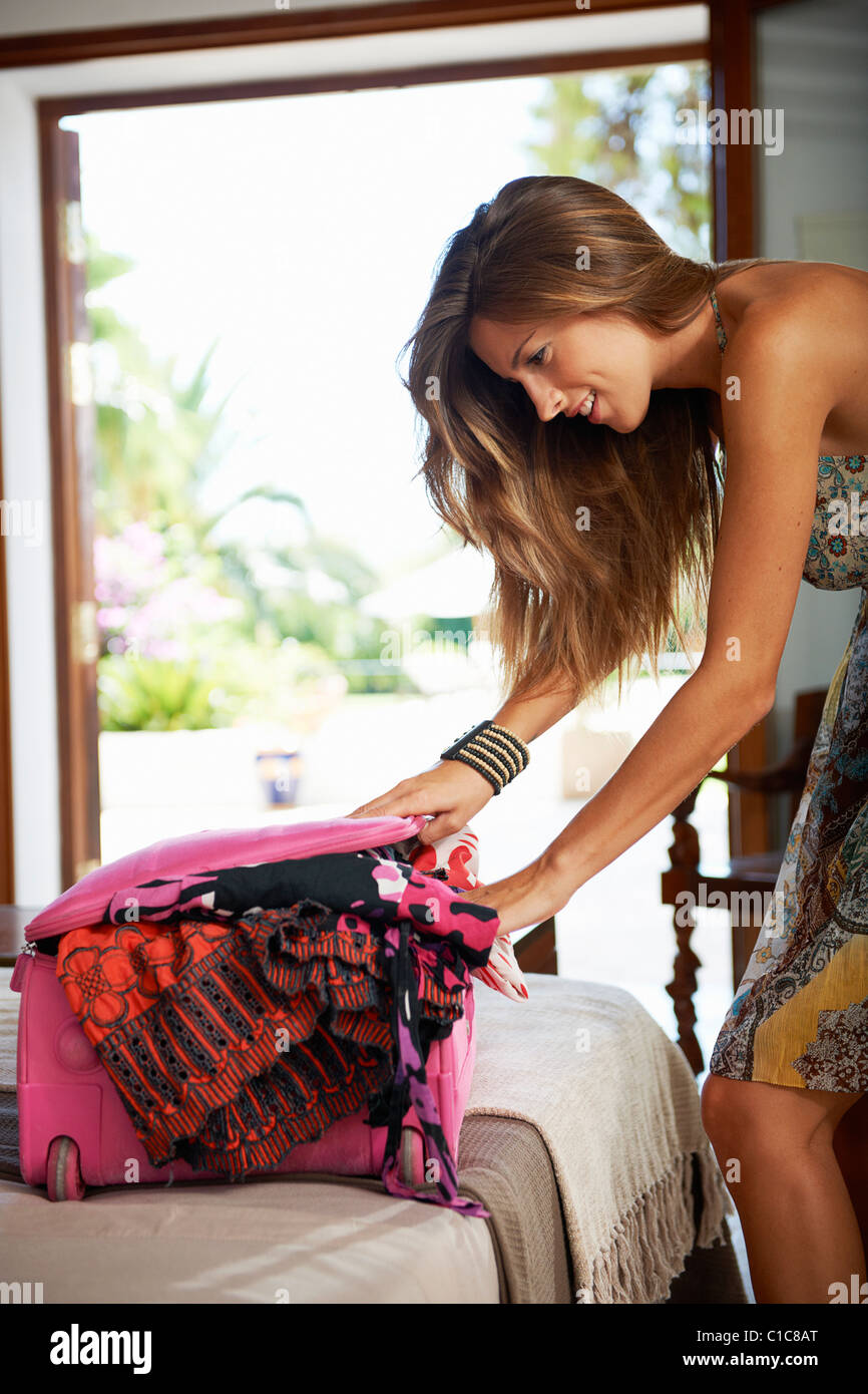 Woman struggling to pack suitcase - Stock Image