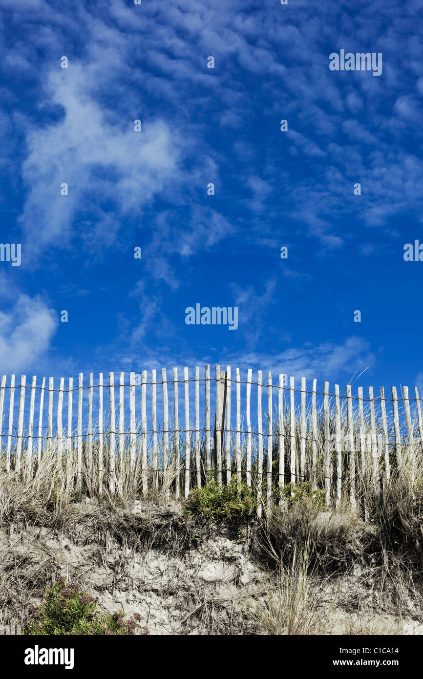 Wooden picket fence on sand dune with blue sky - Stock Image