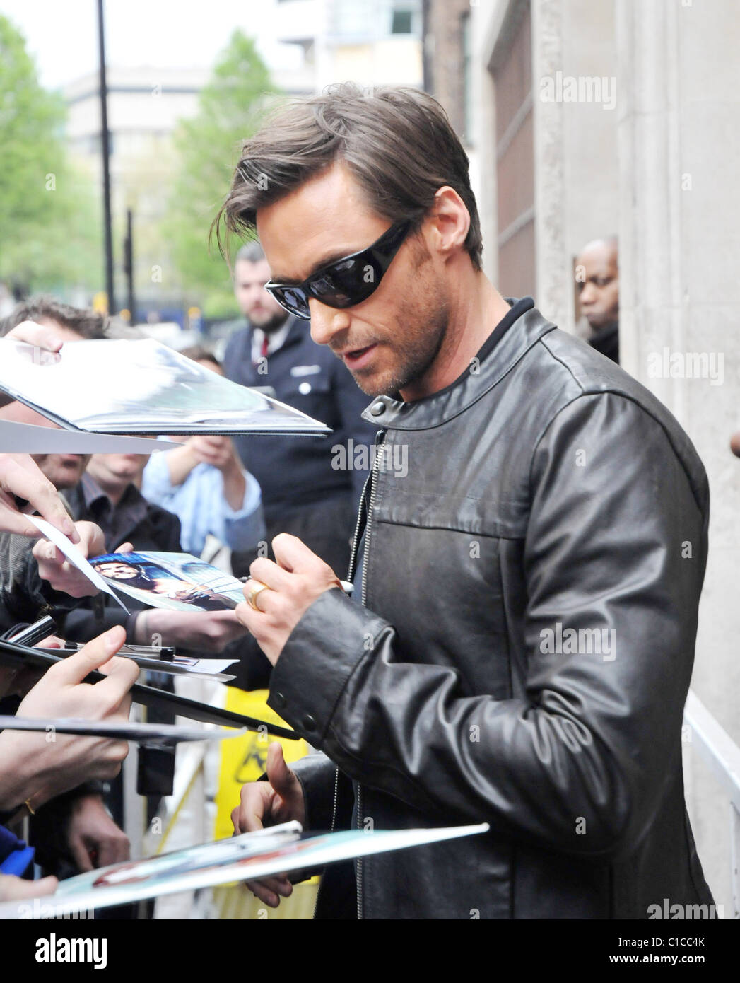Hugh Jackman is happy to sign autographs after being mobbed by fans upon leaving the Radio One studios. The antipodean - Stock Image