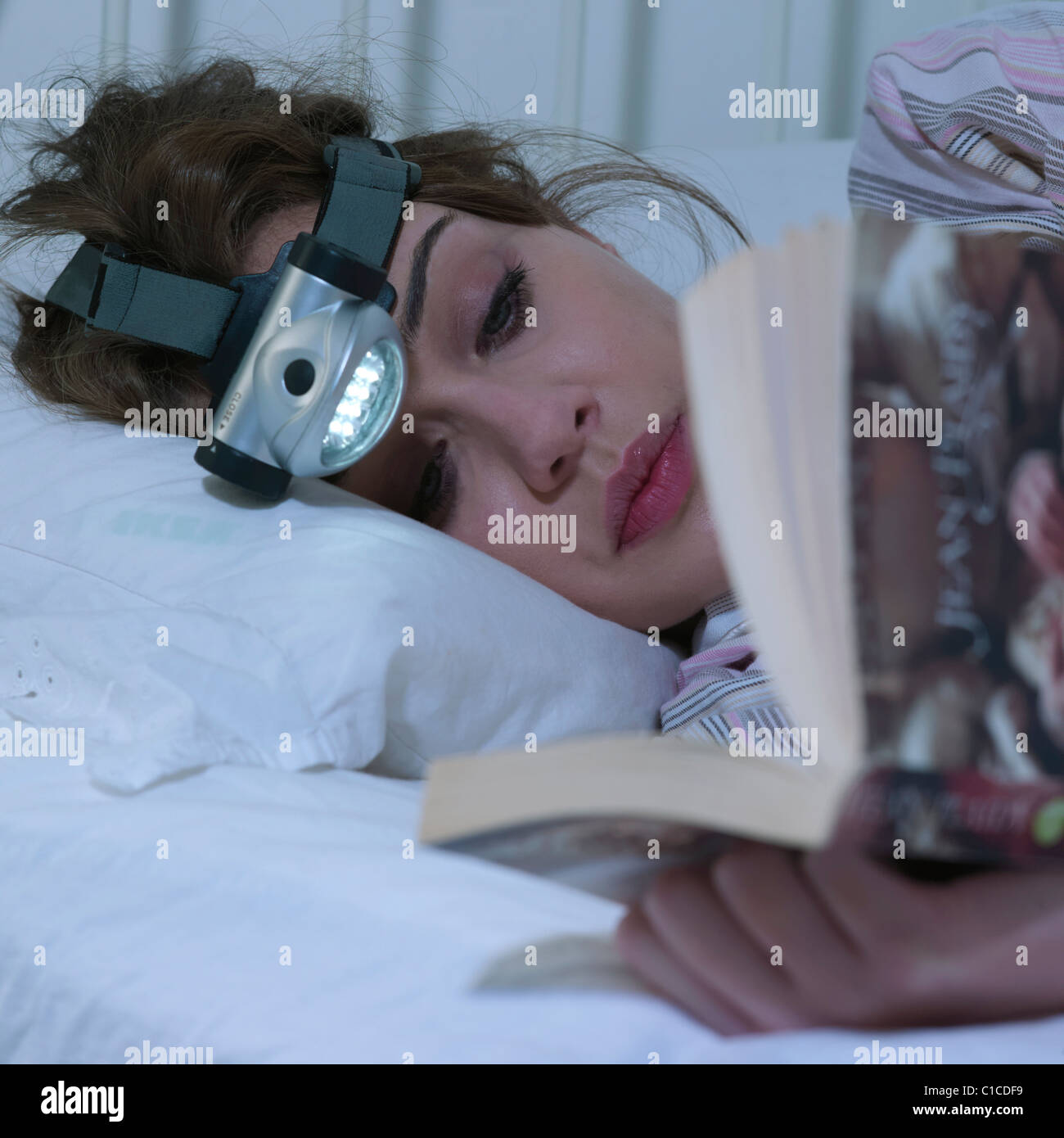 Young woman reading with head torch - Stock Image