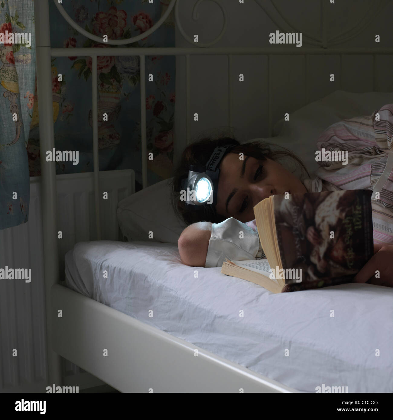 Reading book with head torch - Stock Image