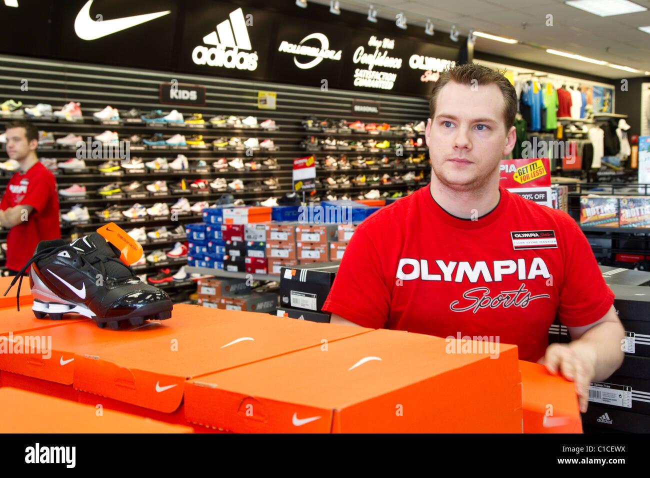 Athletic supply store manager arranges sports clothing placement in athletic sports store - Stock Image
