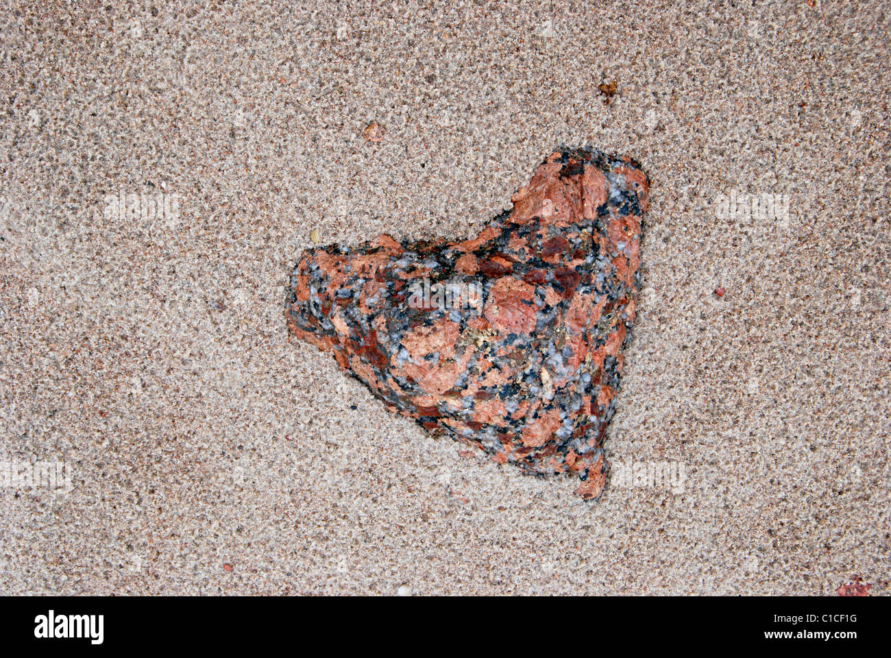 Valentine's stone (hearts form) covered with sand in seashore. - Stock Image