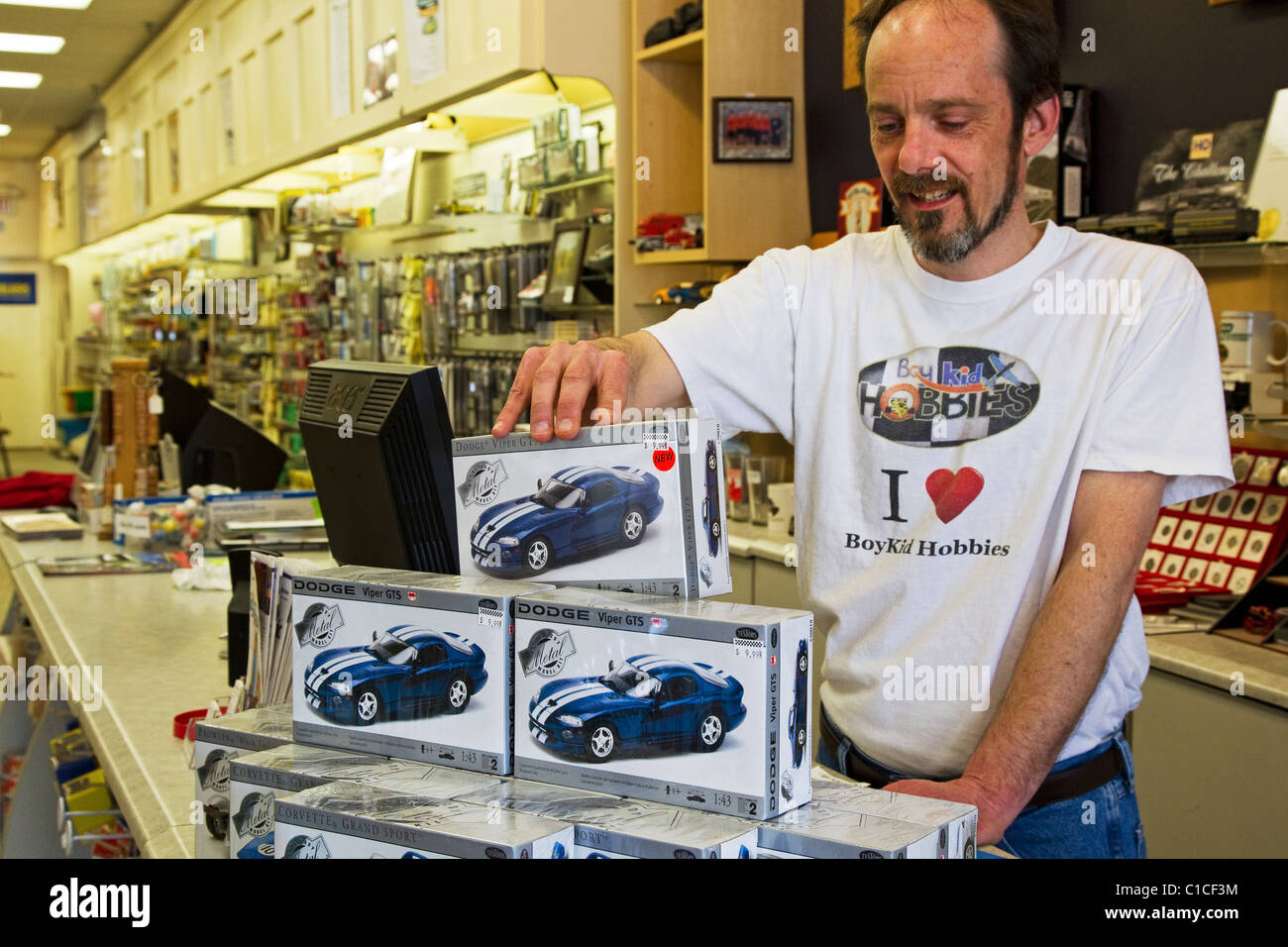 Hobby shop store with retail employee displaying model cars - Stock Image
