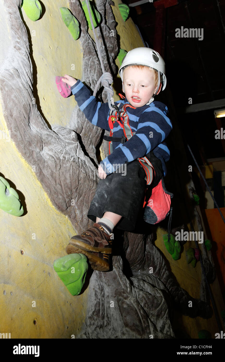 A young boy swinging on a rope at an indoor climbing wall - Stock Image