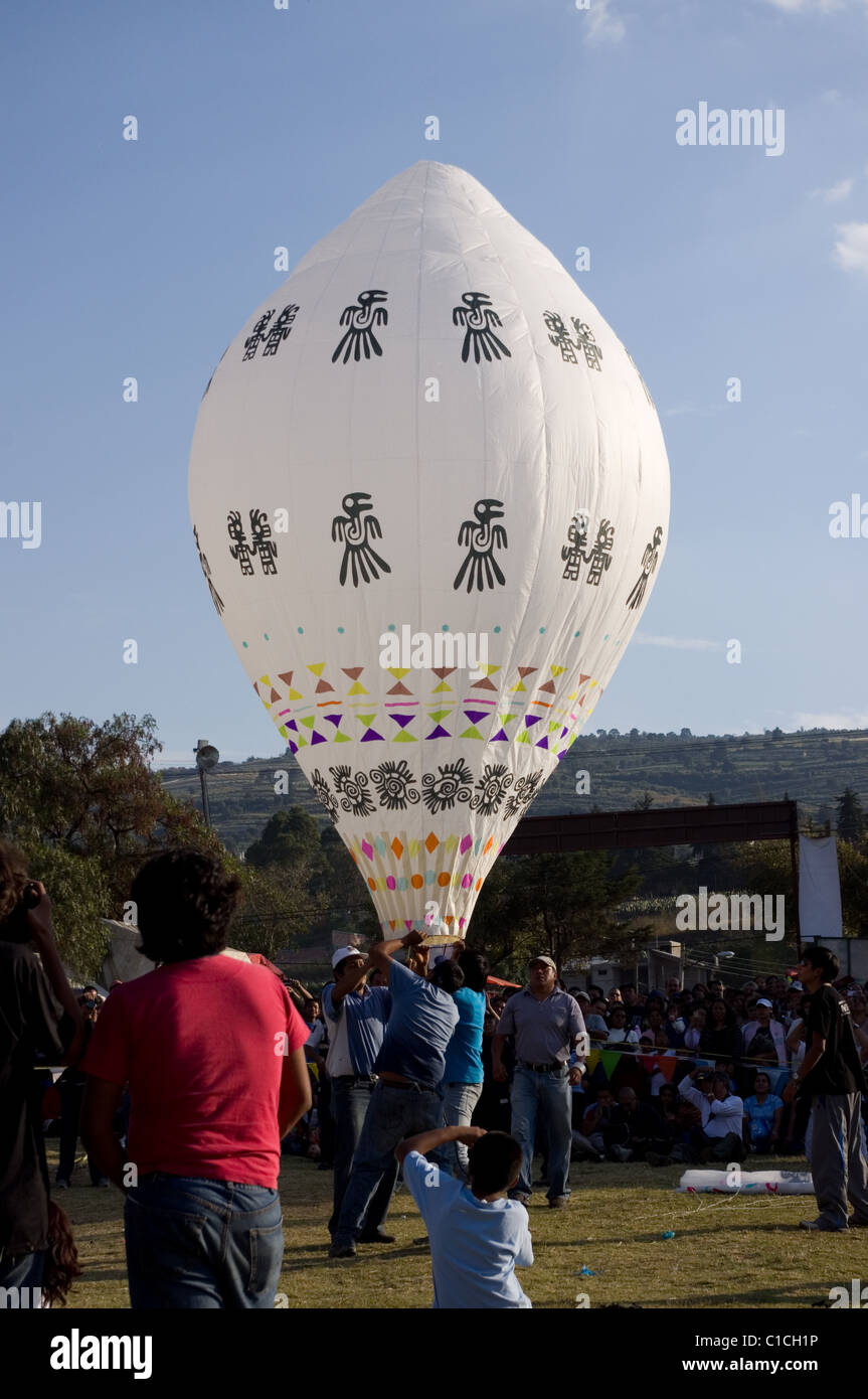 Persons inflating a Globo de Cantolla (hot air paper balloon) with tribal art in San Agustin Ohtenco, Mexico - Stock Image