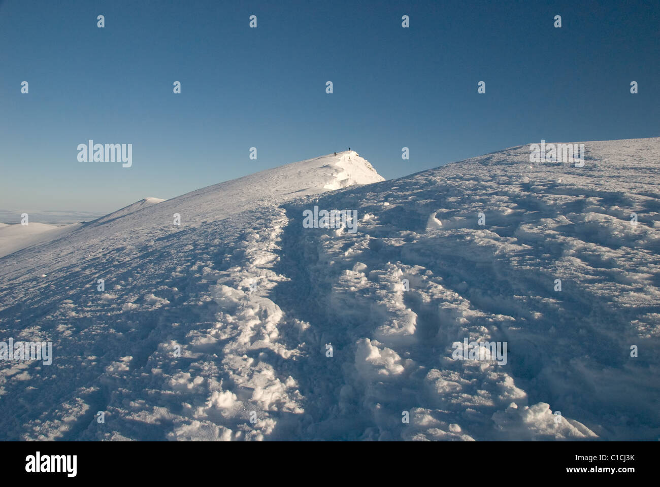 Snowy footpath on the summit ridge of Blencathra in winter n the English Lake District Stock Photo