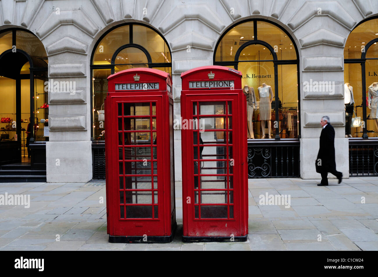 Red Telephone Boxes and L.K. Bennett Clothes Shop, Royal Exchange Buildings, London, England, UK - Stock Image