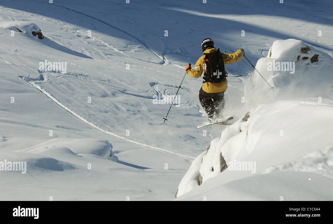 A skier jumps off rocks whilst skiing off piste in the ski resort of Courchevel, France. - Stock Image