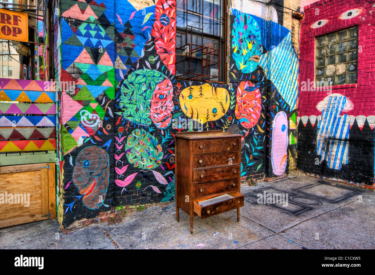 Abandoned chest of drawers sits next to a graffiti covered building in Williamsburg, Brooklyn - Stock Image