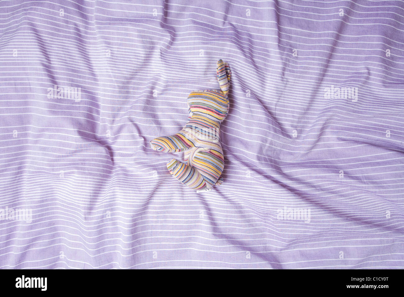 Purple duvet With Toy - Stock Image