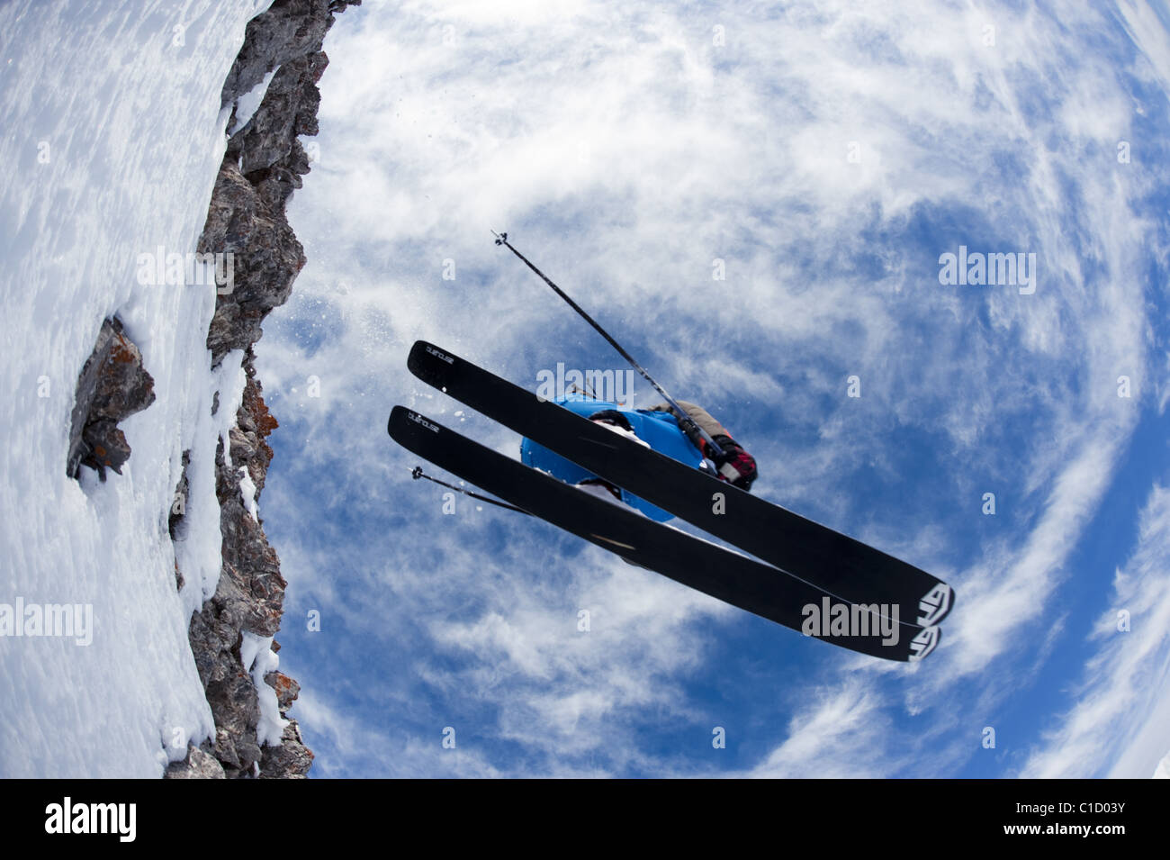 A free skier dropping down a cliff in Argentera, Italy. The skier is flying above the photographer. - Stock Image