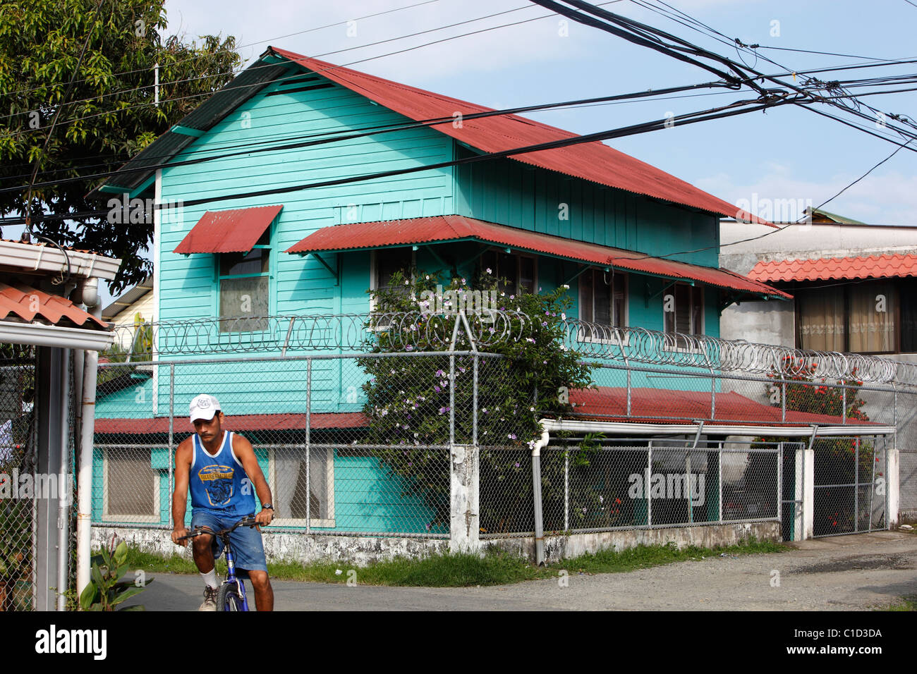 A man rides a bicycle past a house surrounded by a fence and razor ...