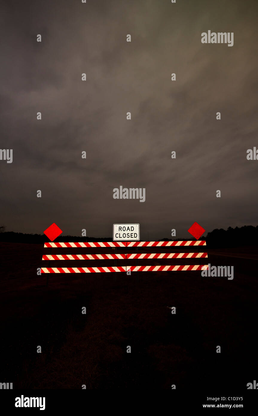 Road Closed sign under a dark stormy sky in Mount Olive, Mississippi - Stock Image
