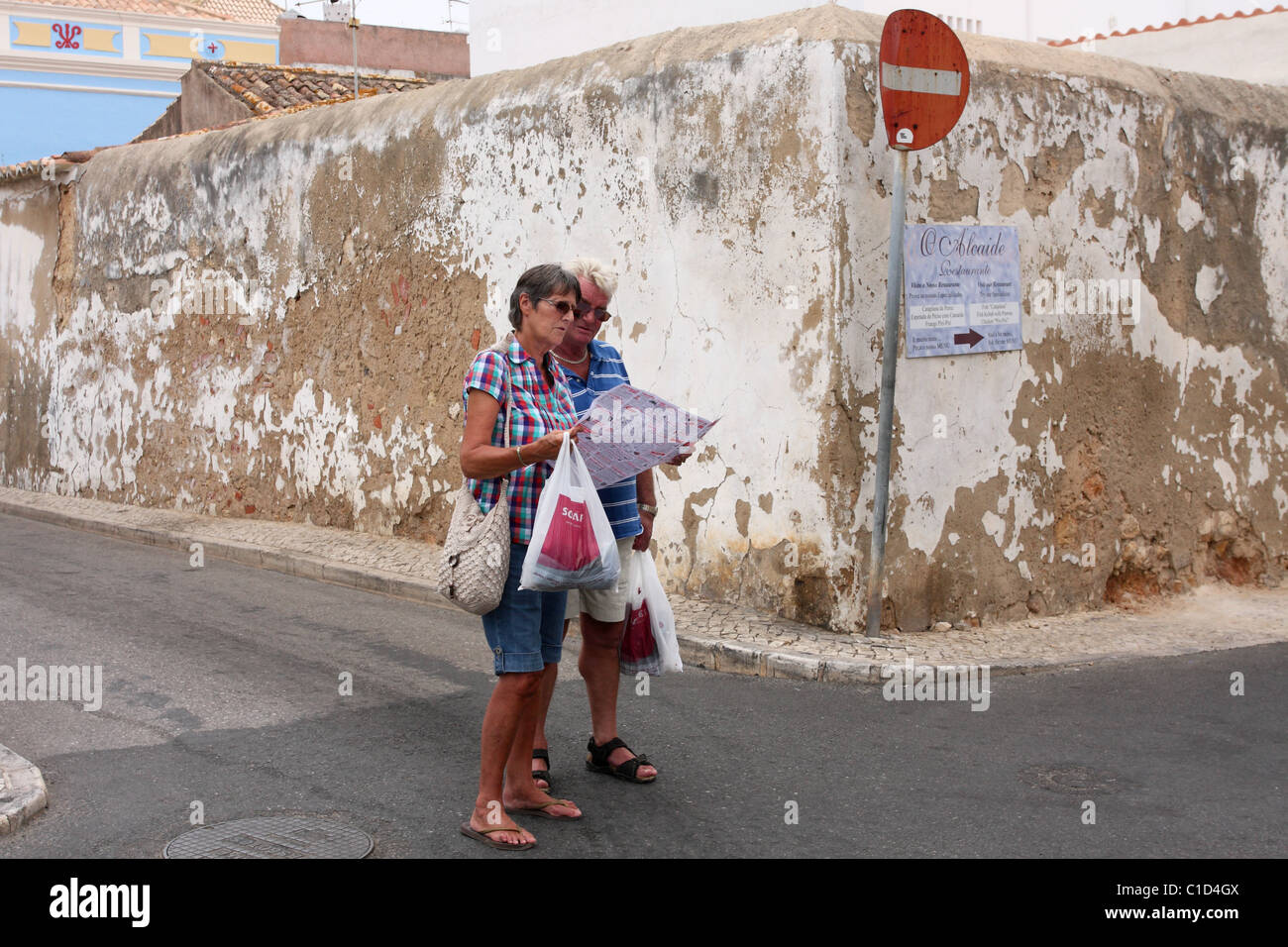 Two tourists look at the map at a crossroads. Alvor, Algarve, PORTUGAL - Stock Image
