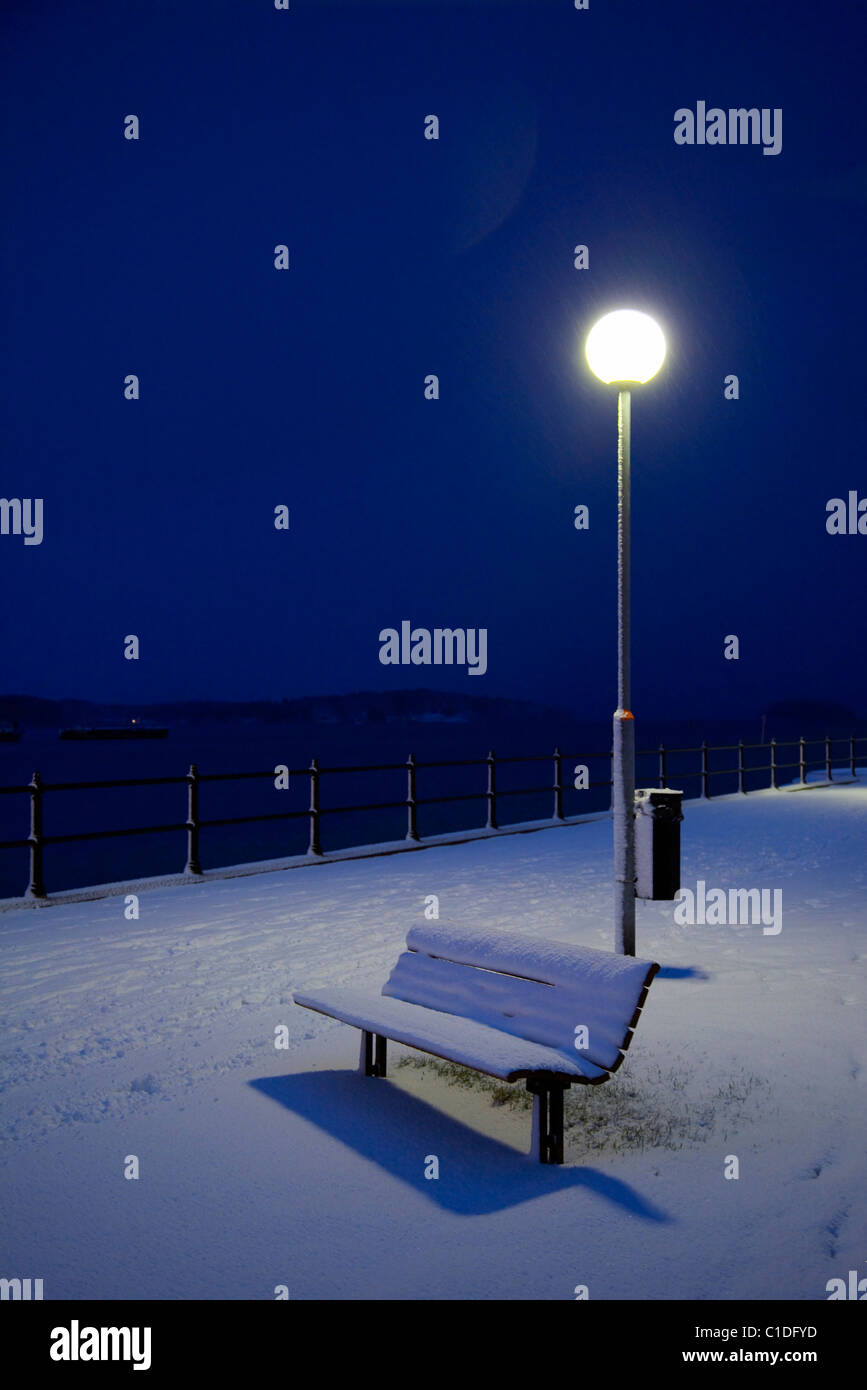 Park bench covered in snow at night - Stock Image