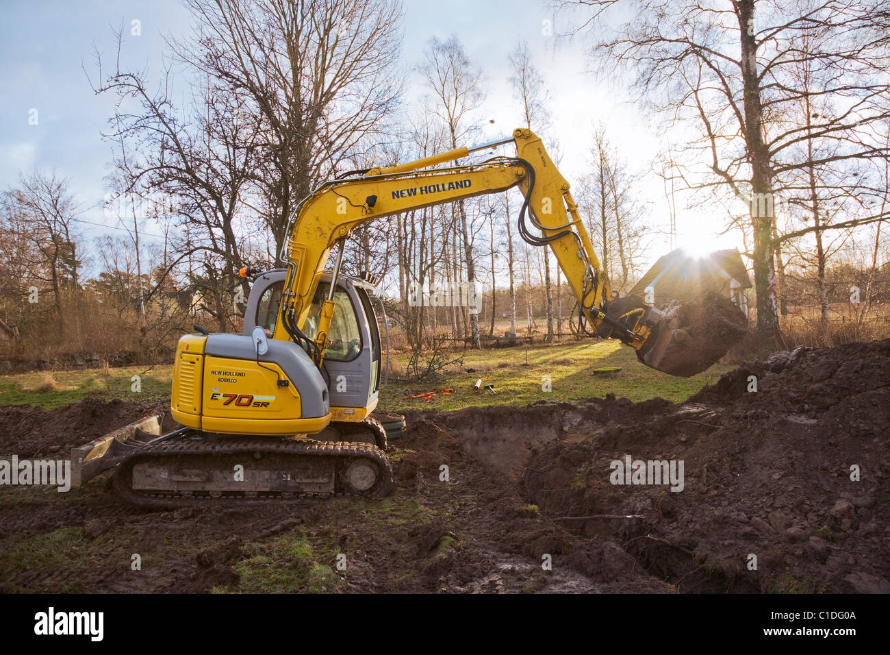 The sun rising behind a New Holland excavator digging up mud in a rural garden. - Stock Image