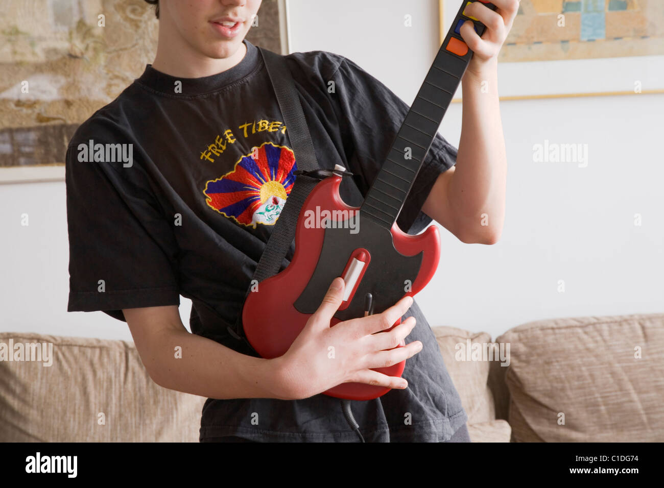 A teenage boy playing the Playstation game Guitar Hero wearing a Free Tibet-T-shirt. - Stock Image