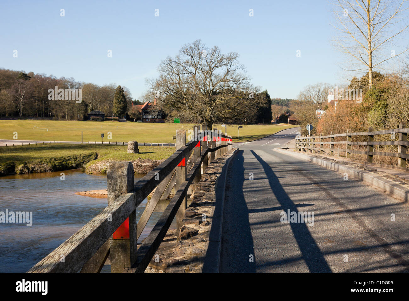 Tilford, Surrey, England, UK. View to village green along the narrow bridge across the River Wey. - Stock Image