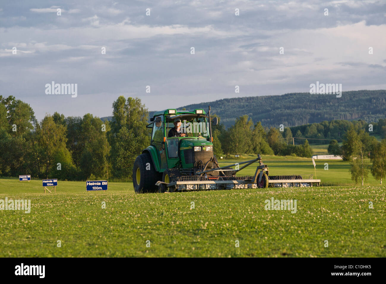 Tractor gathering golf balls at a driving range at the end of the day in Varmland, Sweden. - Stock Image
