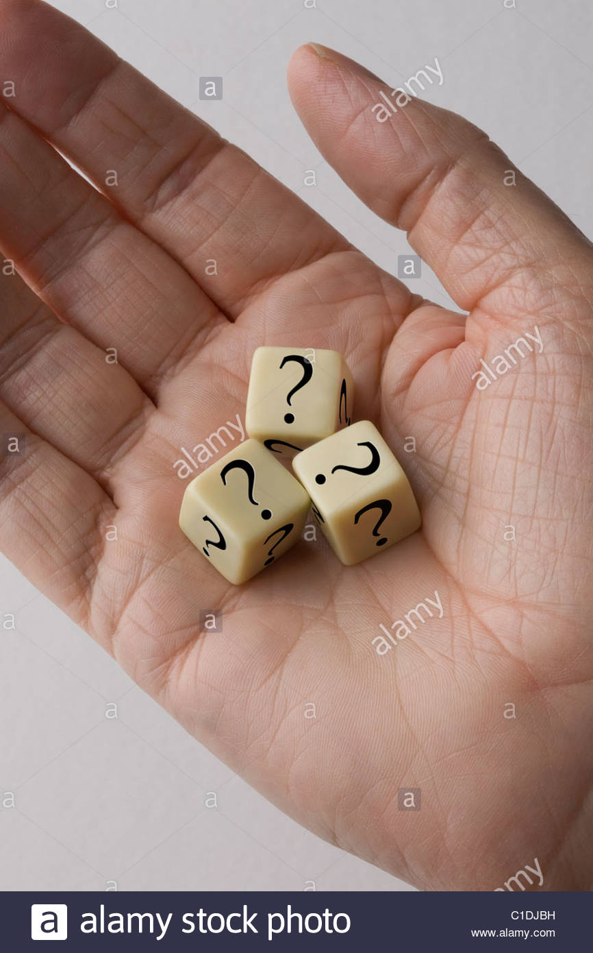 Three dice with questions marks on them in the palm of a mans hand. - Stock Image