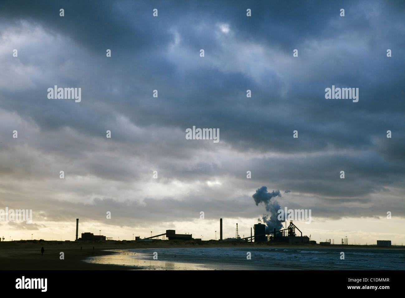 Redcar steelworks outline against dark forbidding sky - Stock Image