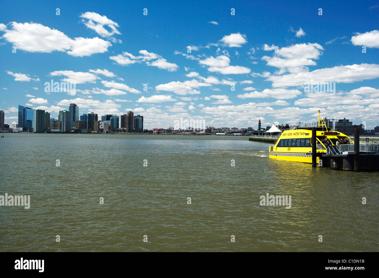 New York Skyline and a yellow water taxi on the Hudson River - Stock Image