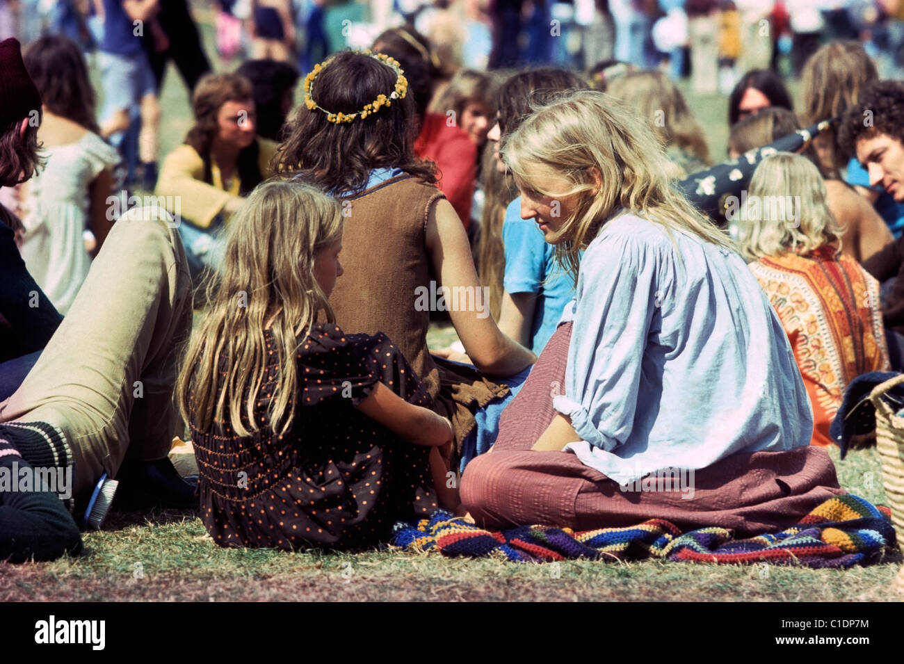 Woman talking to girl in a crowd of hippies sitting in a ...