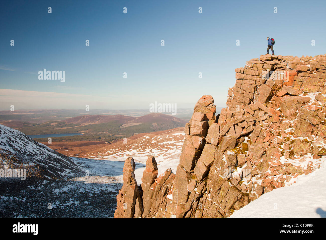 A mountaineer on a rocky granite outcrop above Coire an Lochain in the Cairngorm Mountains, Scotland, UK. - Stock Image