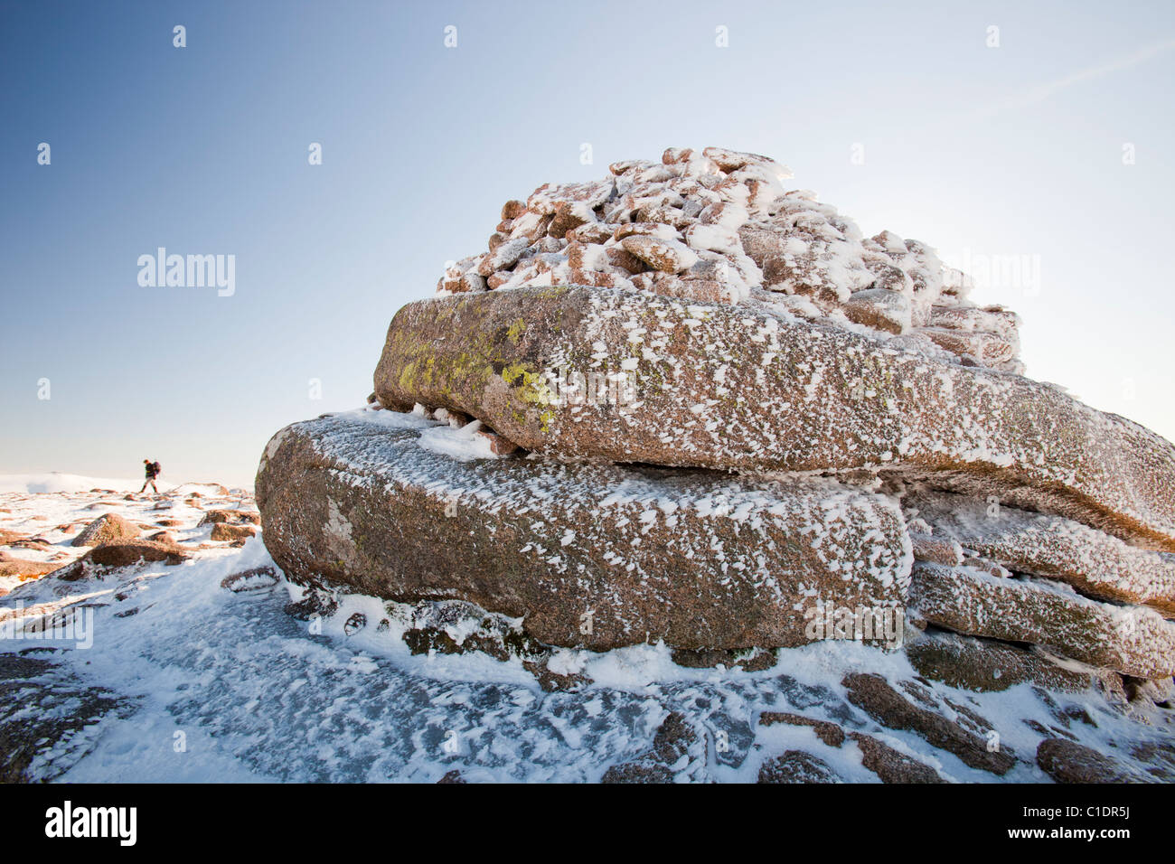 A cairn covered in hoare frost on the Cairngorm Plateau, Scotland, UK, with a mountaineer in the background. - Stock Image