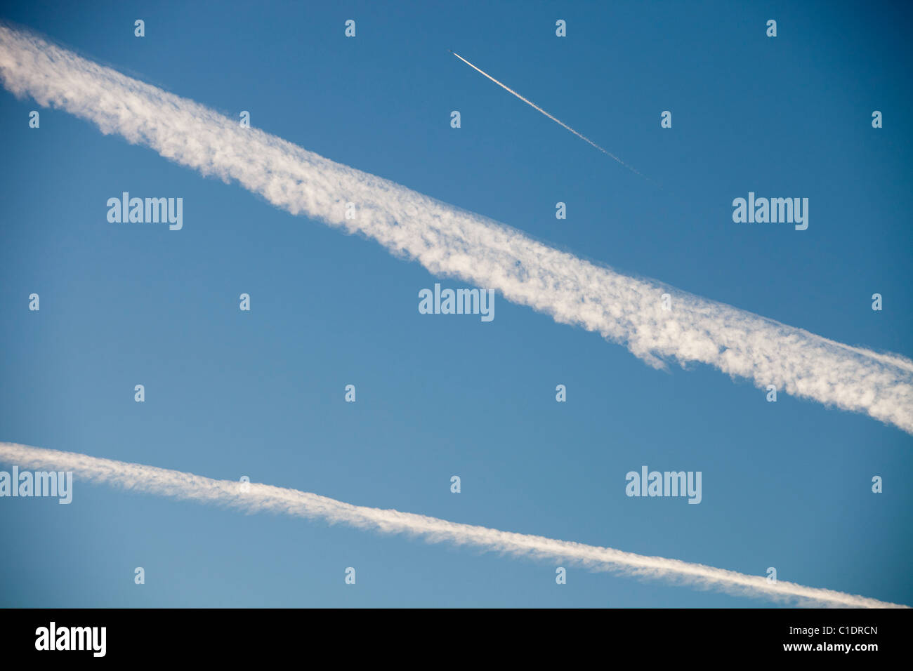 A jet plane flying over the Lake District, UK, with contrails in the sky. - Stock Image