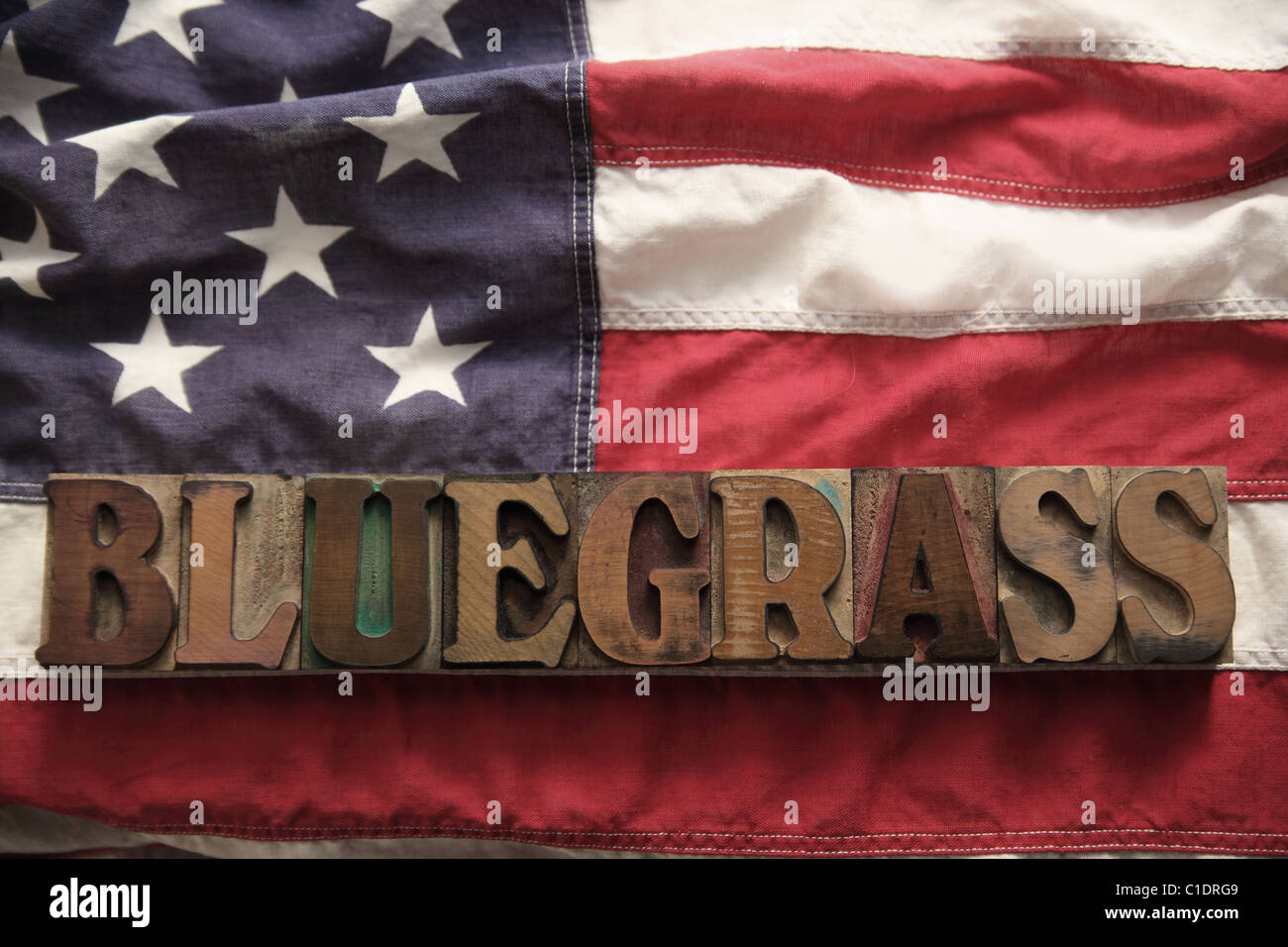 an American flag with the word bluegrass in old wood type - Stock Image