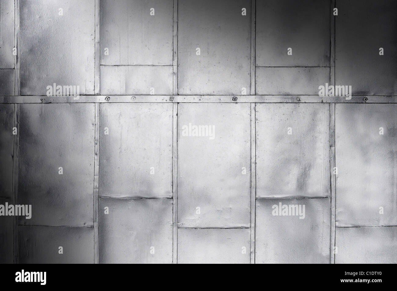 Metal panels on industrial door or wall lit diagonally - Stock Image