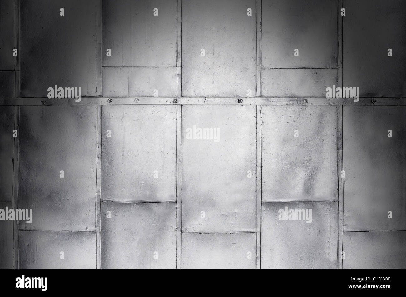 Metal panels on industrial door or wall dramatically lit from above - Stock Image