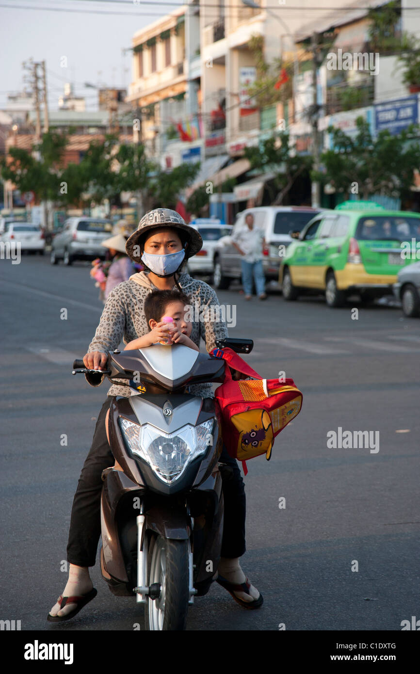 Mother with Pollution Mask and Young Boy without Helmet or Mask - Stock Image