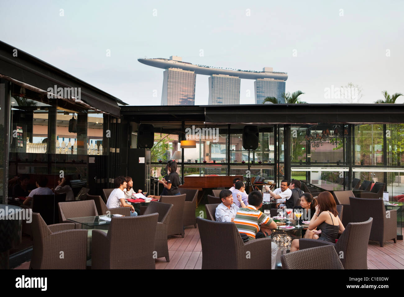Drinks at Orgo Bar & Restaurant with Marina Bay Sands in background.  Marina Bay, Singapore - Stock Image