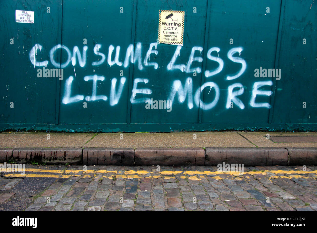 Anti-Capitalist graffiti sprayed onto a wall in Wapping, East London - Stock Image