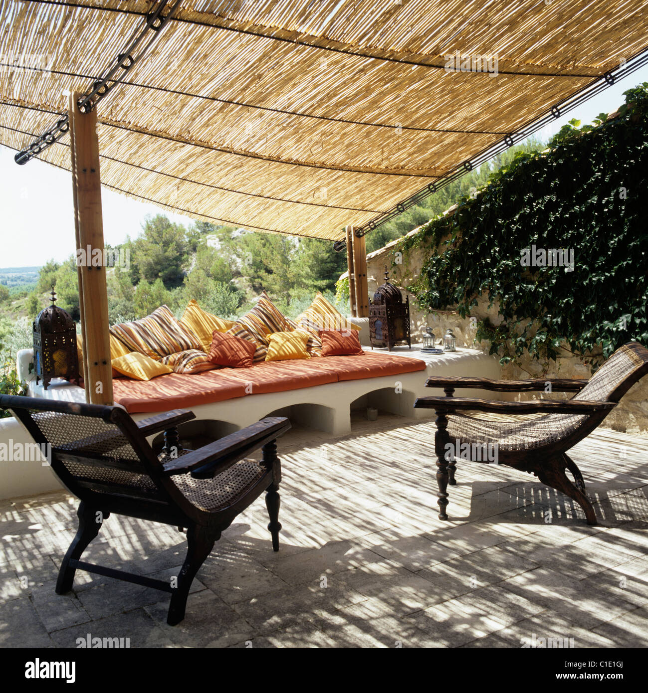 Wooden armchairs and cushioned seating on terrace with bamboo awning and rural Provencal views - Stock Image