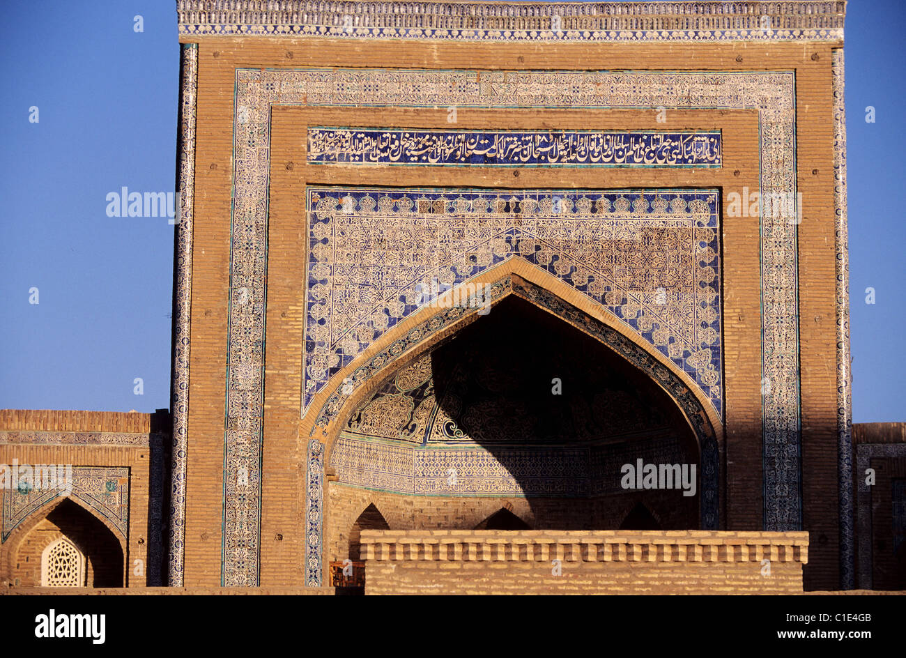 Uzbekistan, Khiva, Monumental door richly adorned with ceramics illustrating verses of the Coran - Stock Image