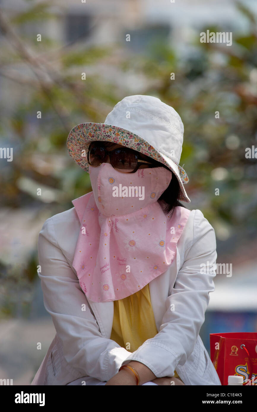 Woman with Elaborate Pink Pollution Mask - Stock Image